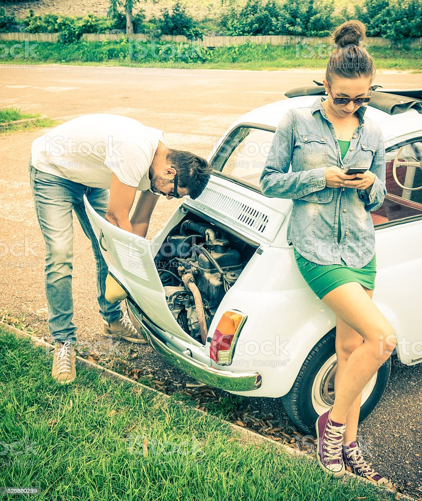 Couple in moment of troubles during a vintage car trip stock photo