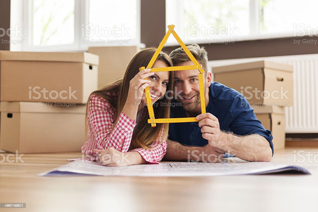Couple in new apartment with home sign stock photo