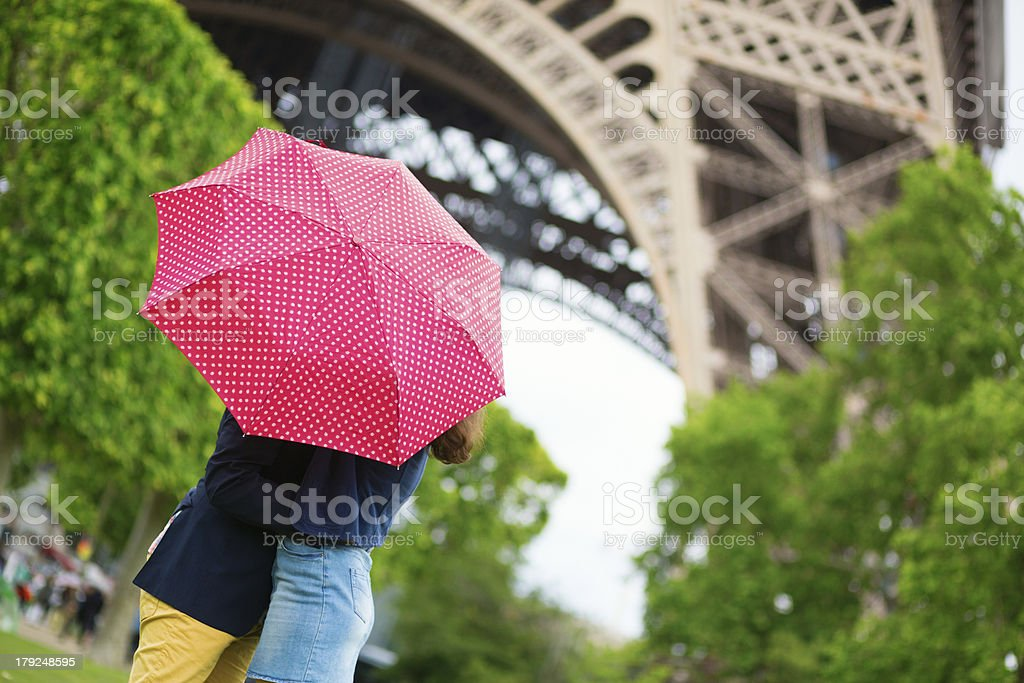 Couple in Paris kissing under the rain royalty-free stock photo