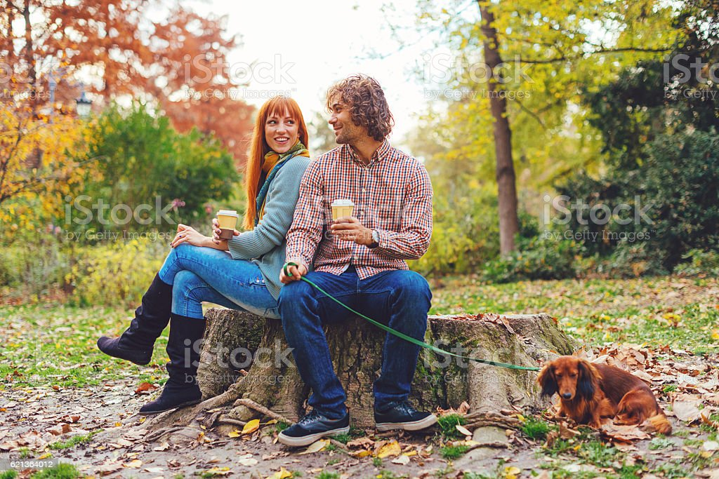 Couple in park with dachshund dog on sunny autumn day stock photo