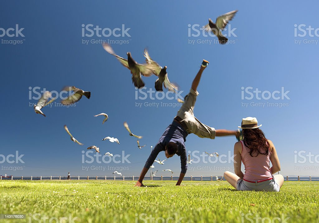 Couple in park with male doing summersaults royalty-free stock photo