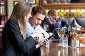 Couple in restaurant using smart phone