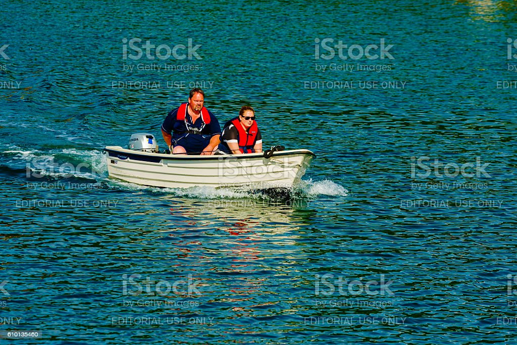 Couple in small motorboat stock photo
