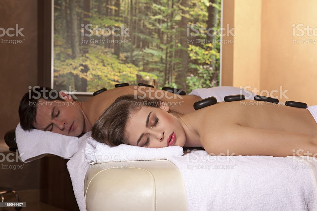 Couple in spa getting stone massage treatment stock photo