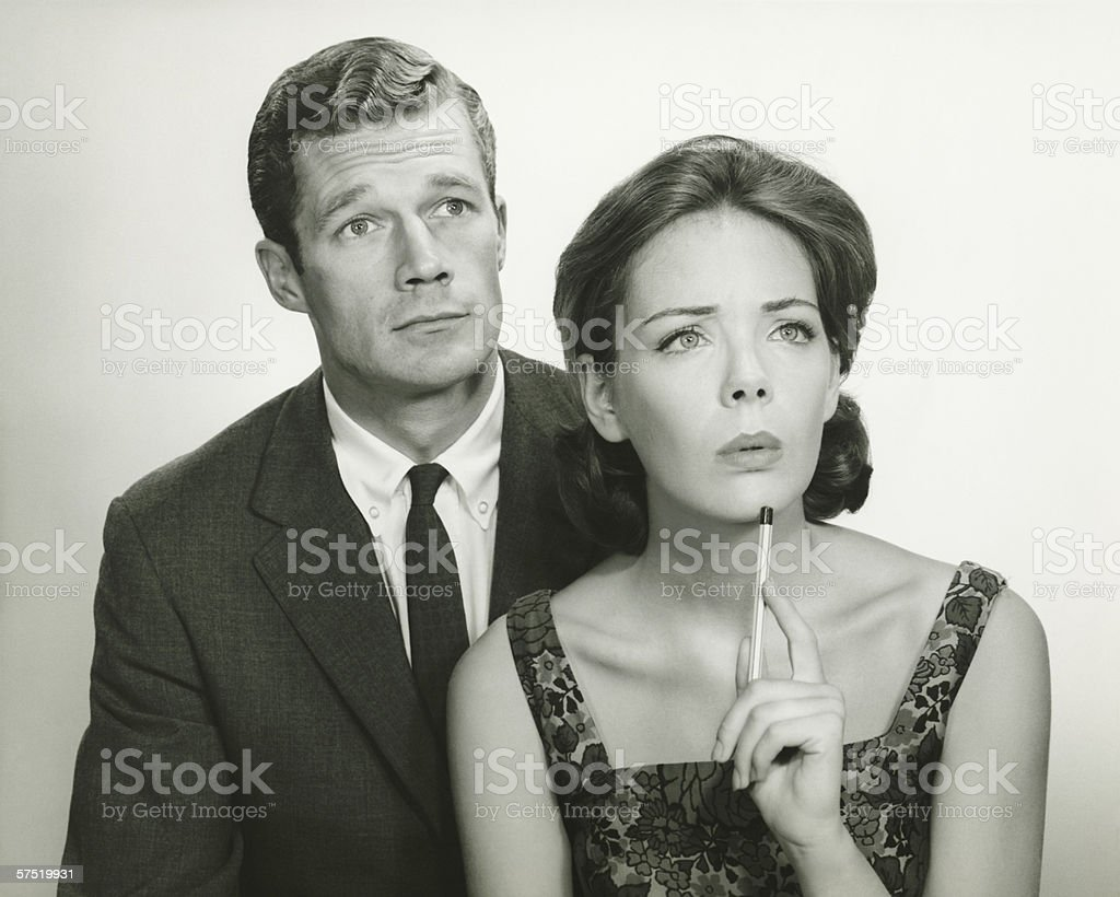 Couple in studio, looking thoughtful, posing (B&W), portrait royalty-free stock photo