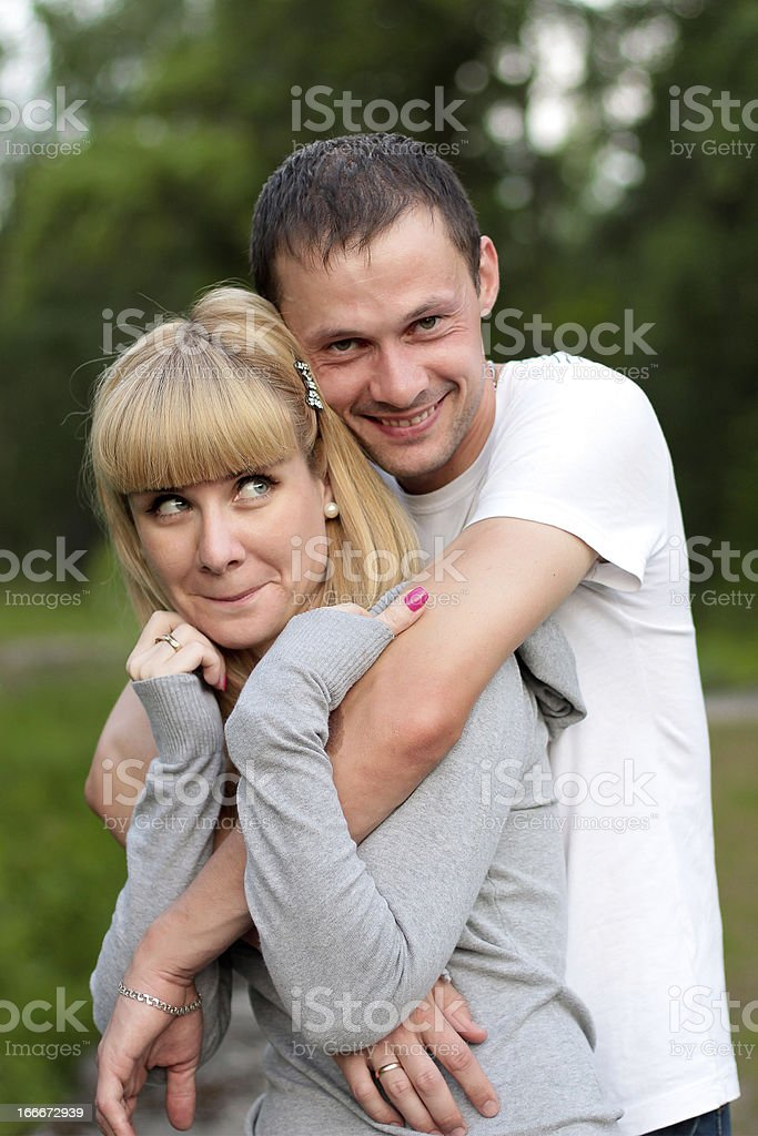 Couple in summer forest smiling she is with crafty look royalty-free stock photo