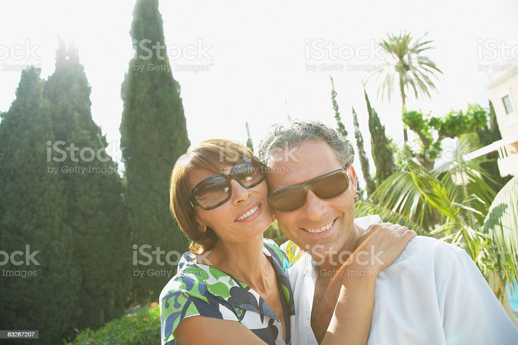 Couple in sunglasses hugging outdoors royalty-free stock photo