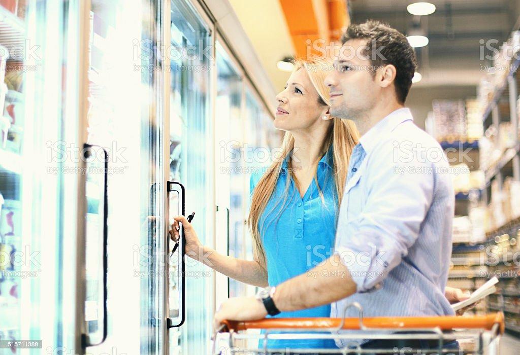 Couple in supermarket buying frozen food. stock photo
