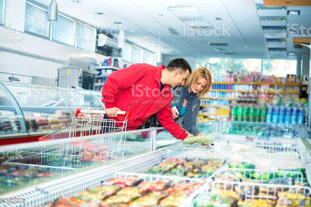 Couple in supermarket near frozen food stock photo