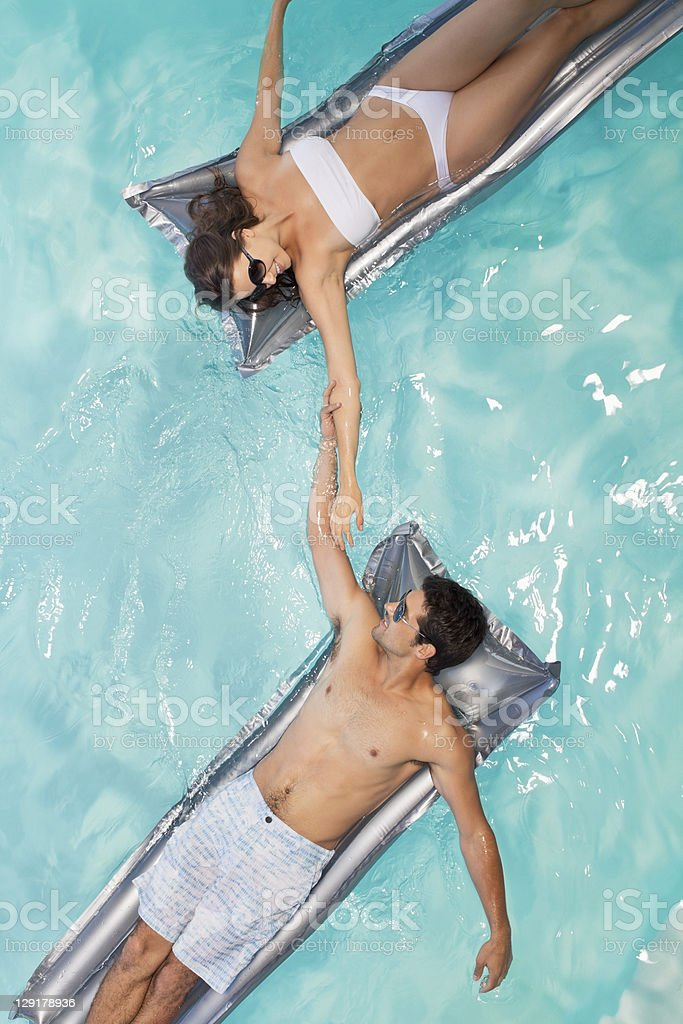 Couple in swimming pool lying on raft royalty-free stock photo