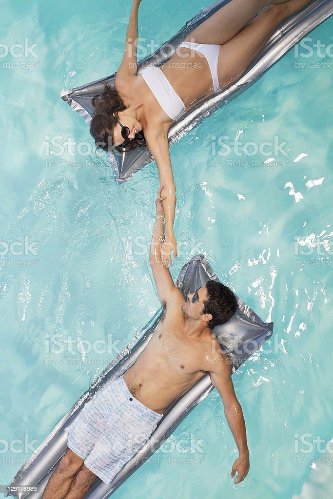 Couple in swimming pool lying on raft stock photo