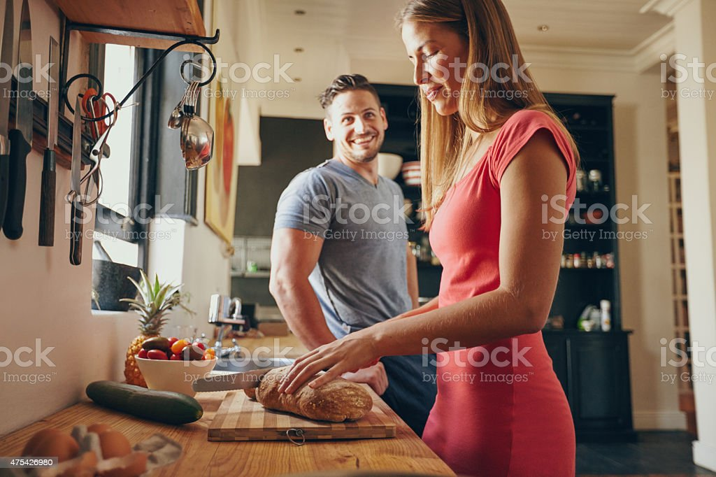 Couple in the kitchen with woman cutting bread stock photo