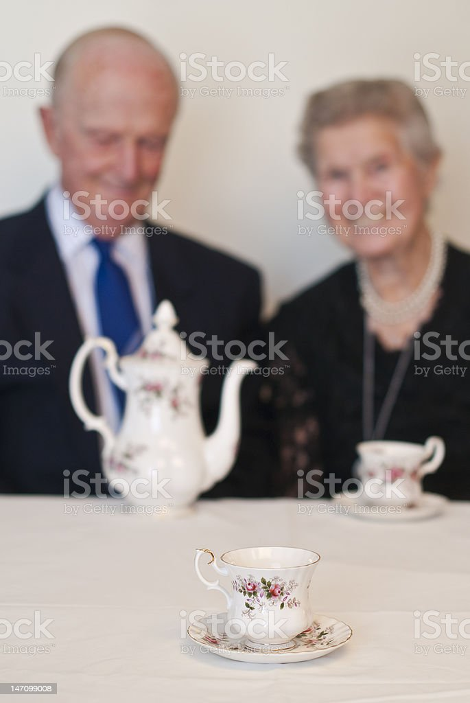 Couple in their eighties enjoying a cup of tea royalty-free stock photo