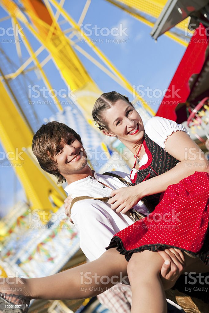 Couple in Tracht flirting at big wheel royalty-free stock photo