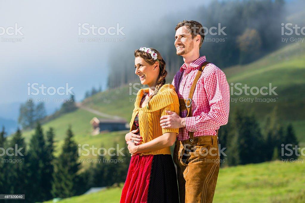 Couple in Tracht on Alp mountain summit at vacation stock photo