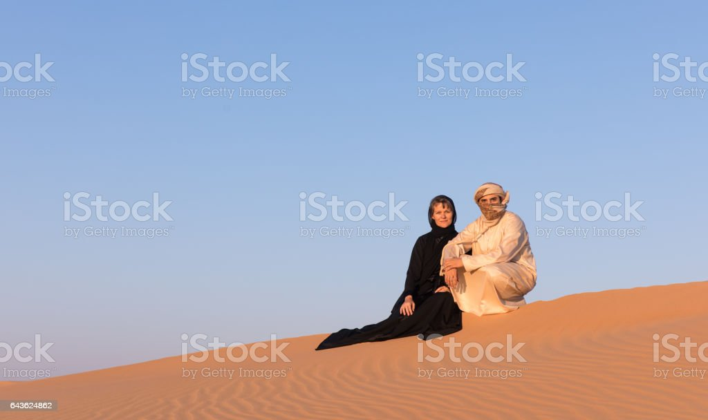 Couple in traditional arab dress in the desert. stock photo
