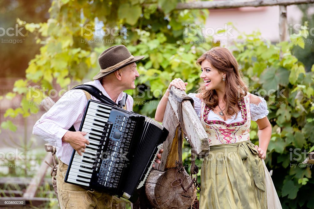 Couple in traditional bavarian clothes with accordion, green gar stock photo