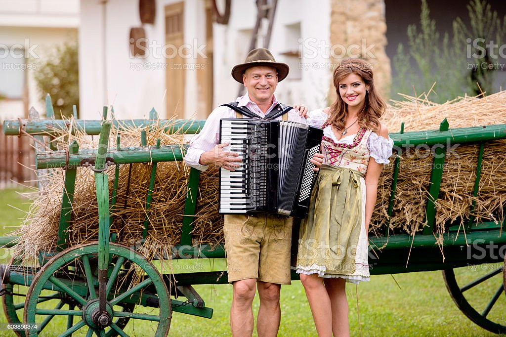 Couple in traditional bavarian clothes with accordion, hay wagon stock photo