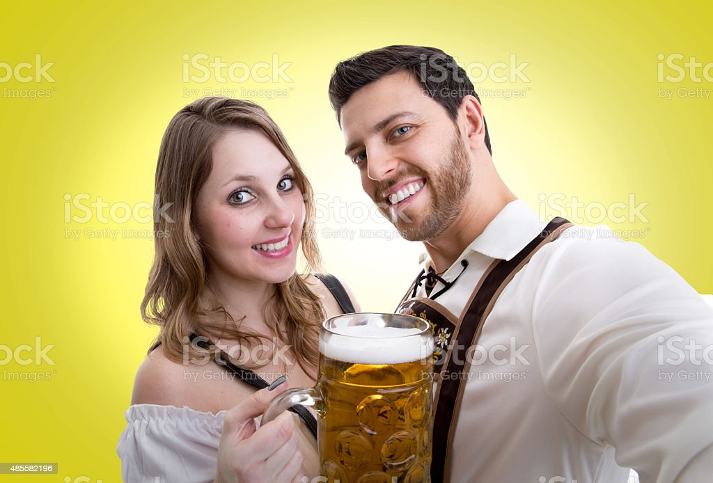 Couple in traditional bavarian costume on yellow background stock photo