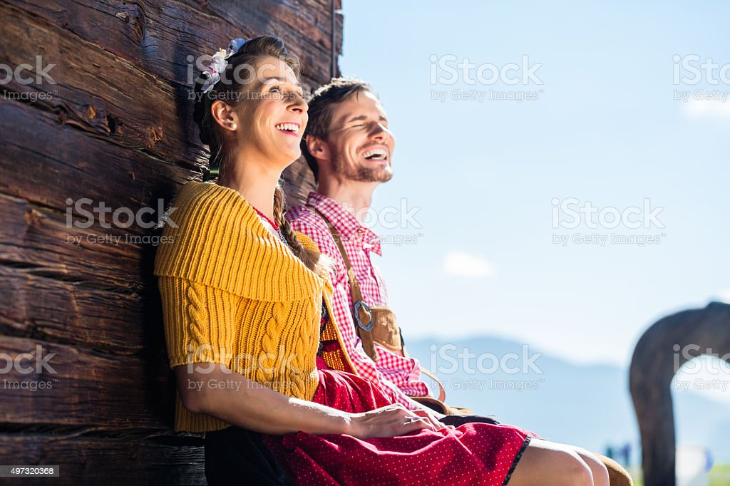 Couple in traditional clothing front of mountain hut stock photo