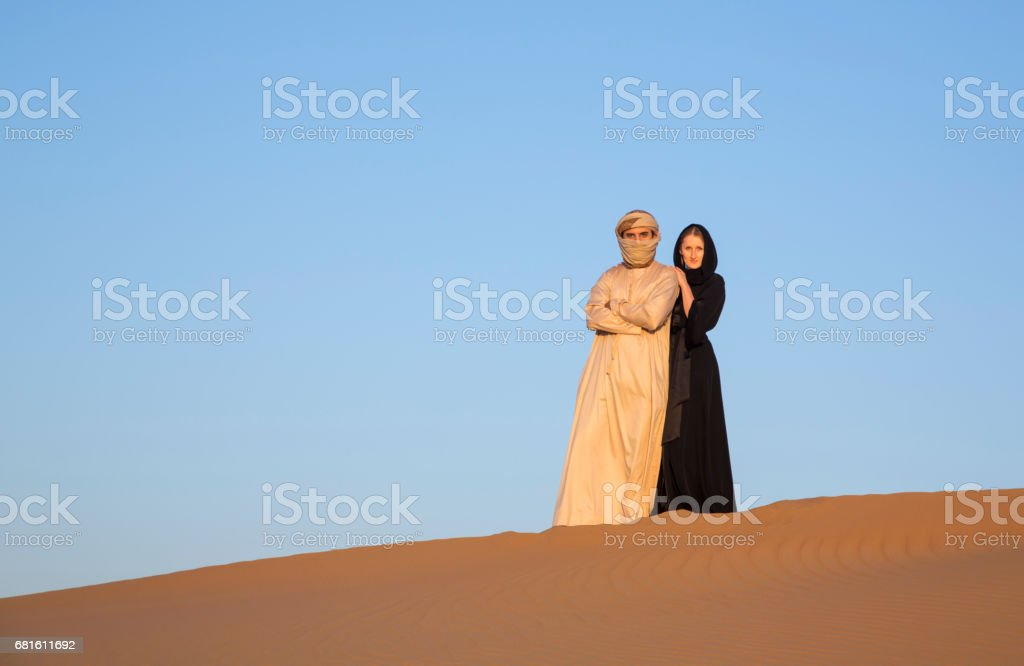 Couple in traditional clothing in a desert near Dubai stock photo