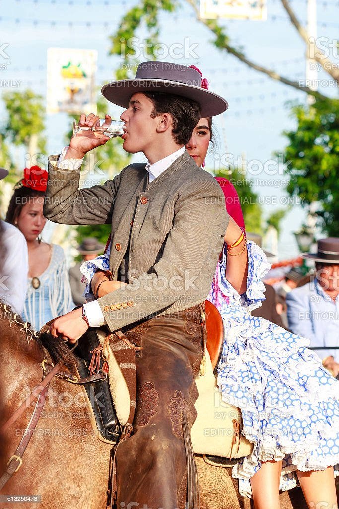 Couple in traditional dress riding at the April Fair Seville. stock photo