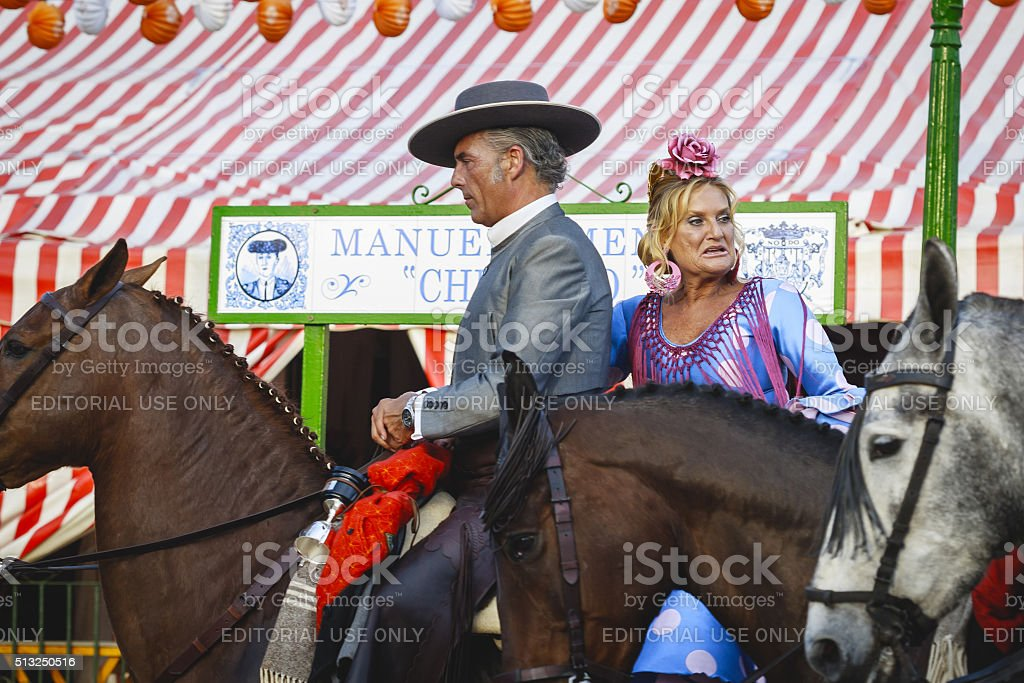 Couple in traditional dress riding at the April Fair Seville stock photo