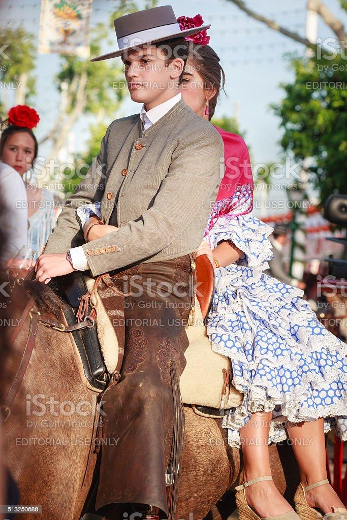 Casal em trajes tradicionais andando na feira de abril em Sevilha foto royalty-free