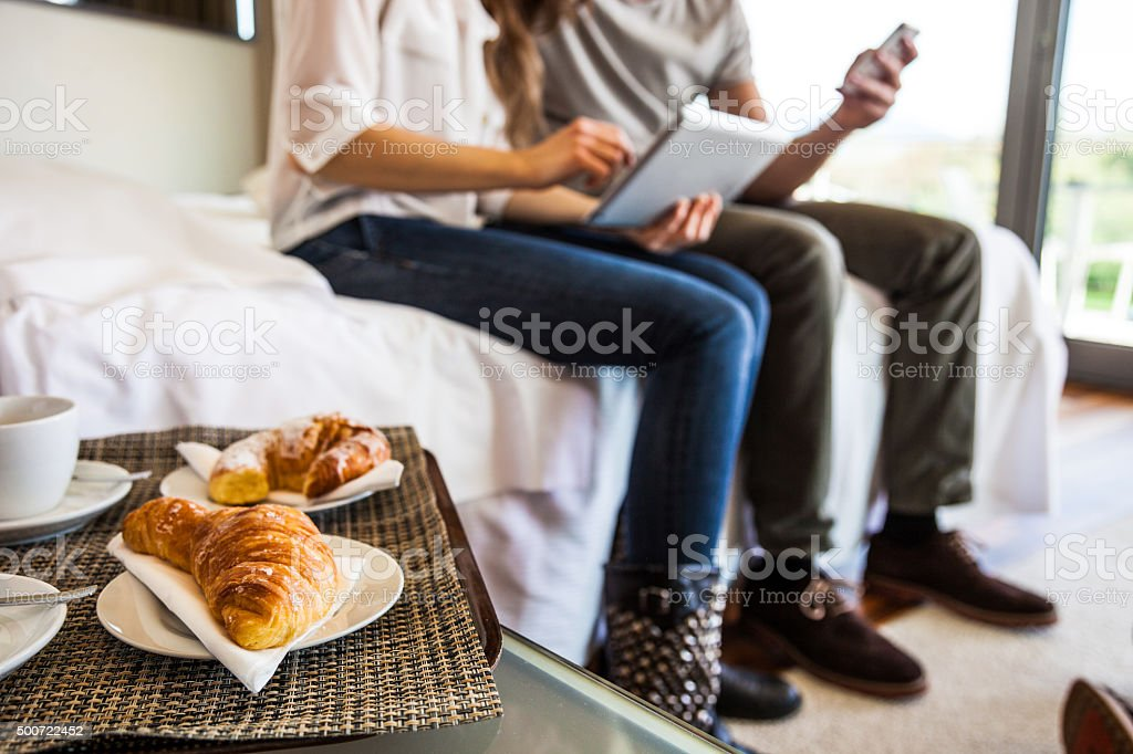 Couple in vacation having breakfast in hotel room stock photo