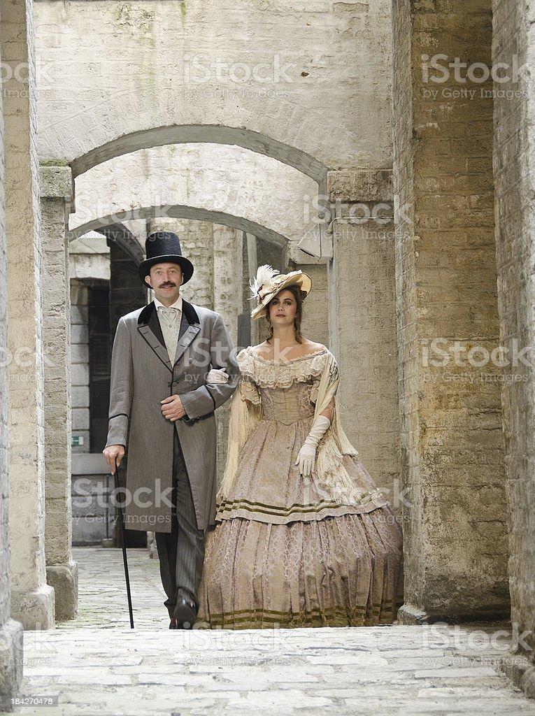 Couple in Victorian costume walking through stone corridor stock photo