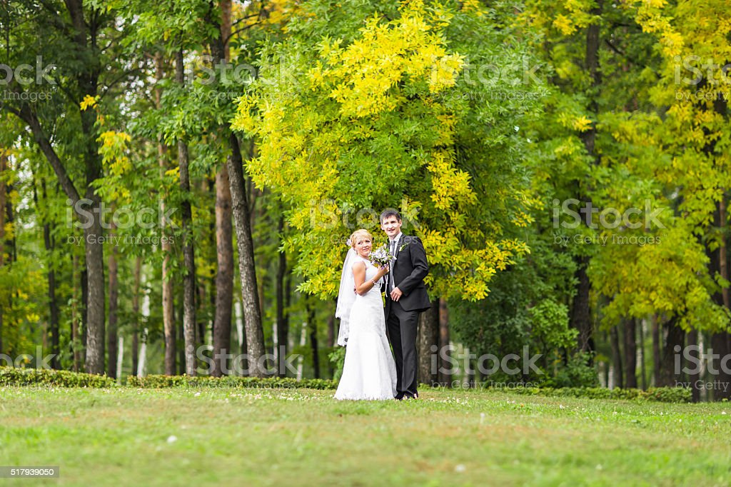 couple in wedding attire with a bouquet of flowers, bride stock photo