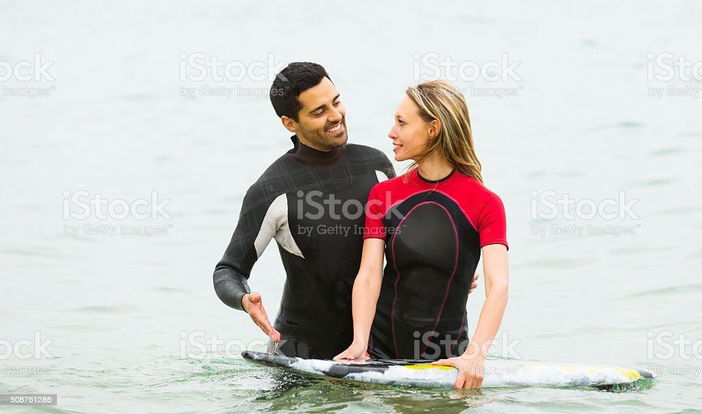 Couple in wetsuits with surf boards stock photo