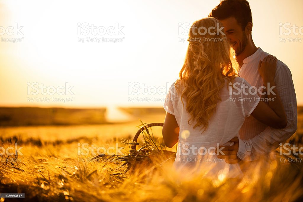 Couple in wheat field at sunset stock photo