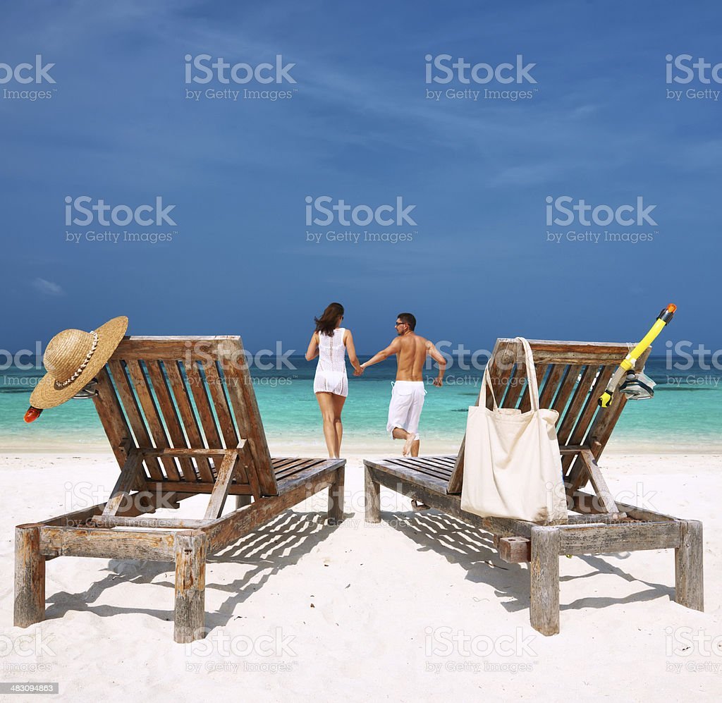 Couple in white running on a beach at Maldives royalty-free stock photo