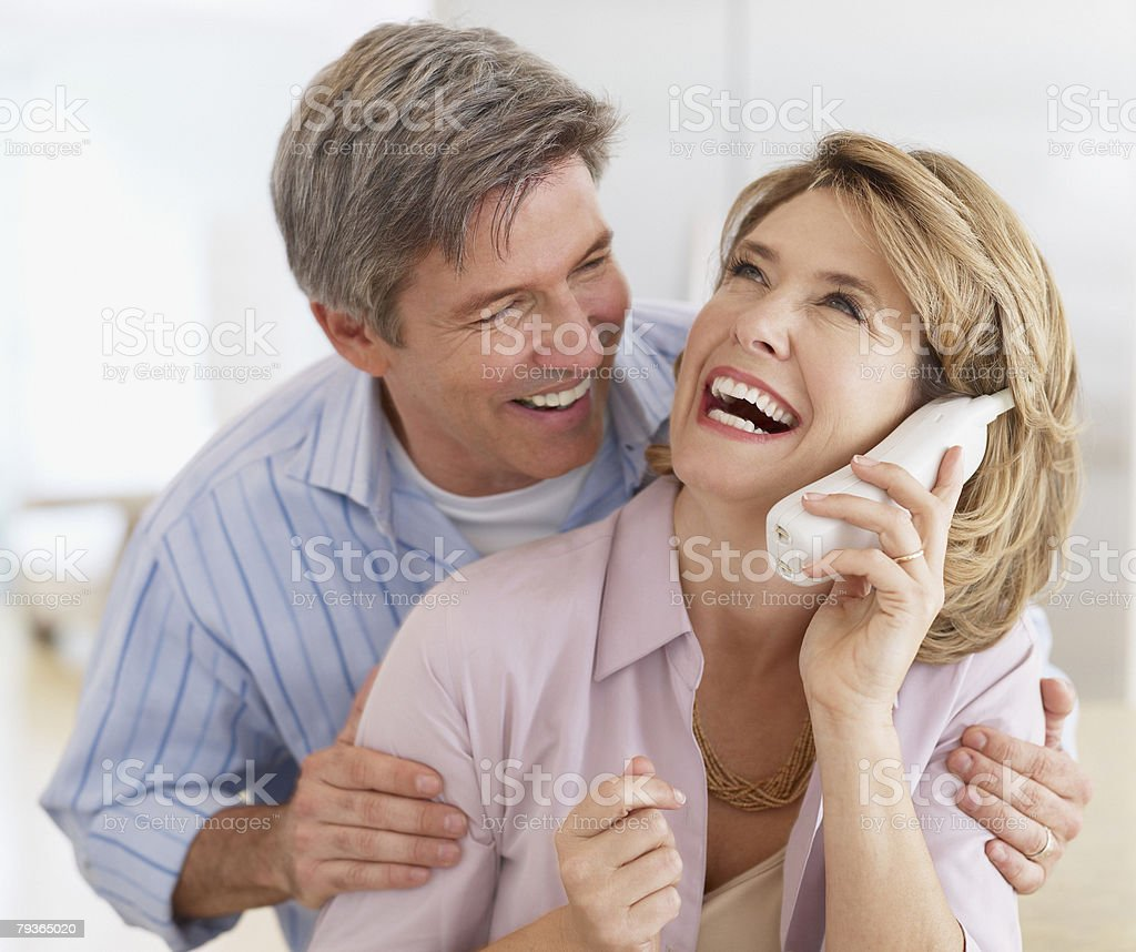 Couple indoors with a telephone laughing stock photo