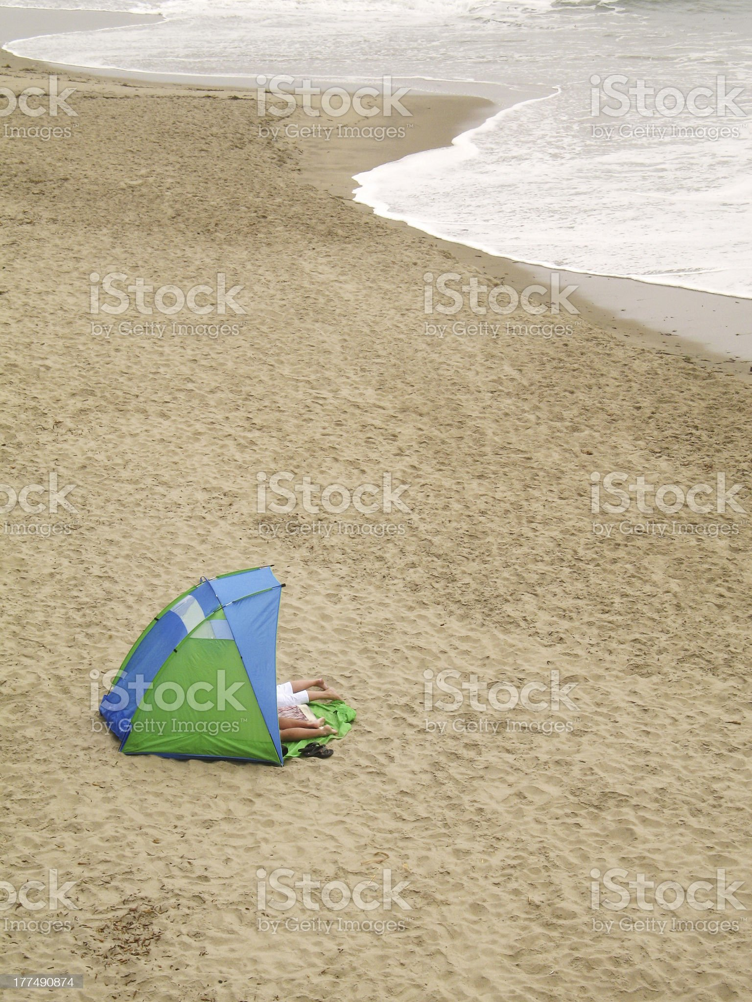 Couple inside a tent with feet outside on the beach royalty-free stock photo