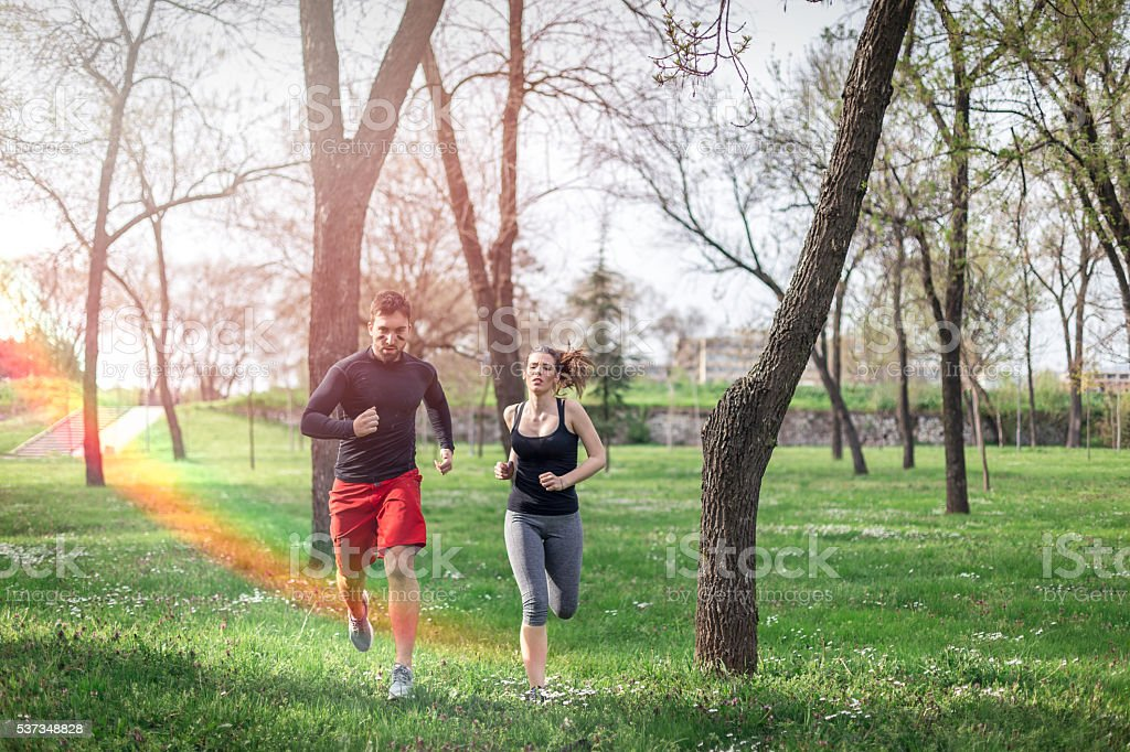 couple is running in park after rain stock photo