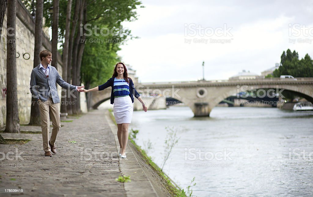 Couple is walking by the Seine embankment in Paris royalty-free stock photo