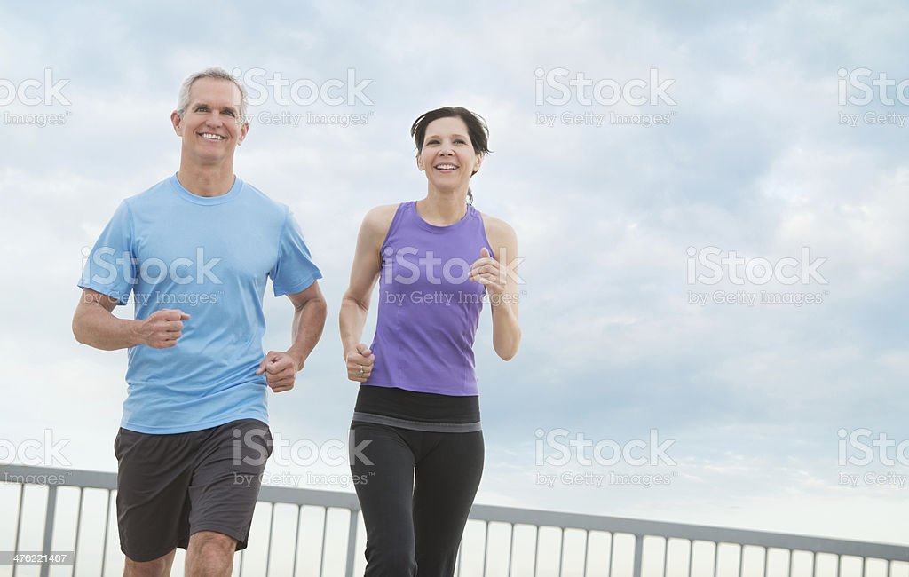 Couple Jogging Against Cloudy Sky stock photo