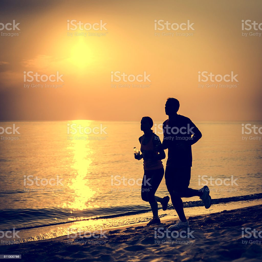 Couple jogging at the sandy beach stock photo
