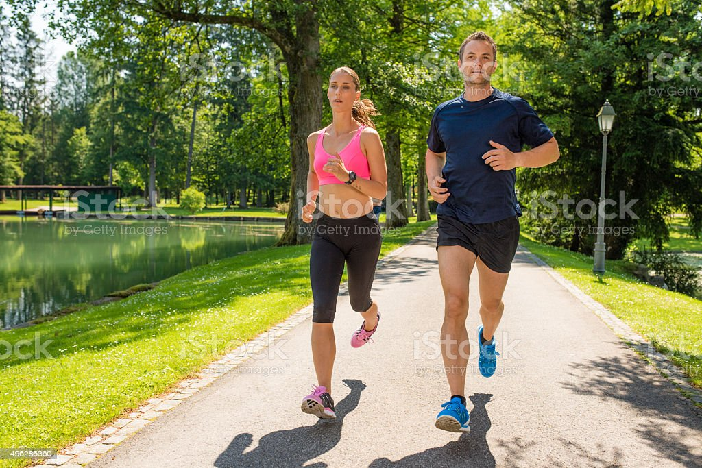 Couple jogging in park stock photo