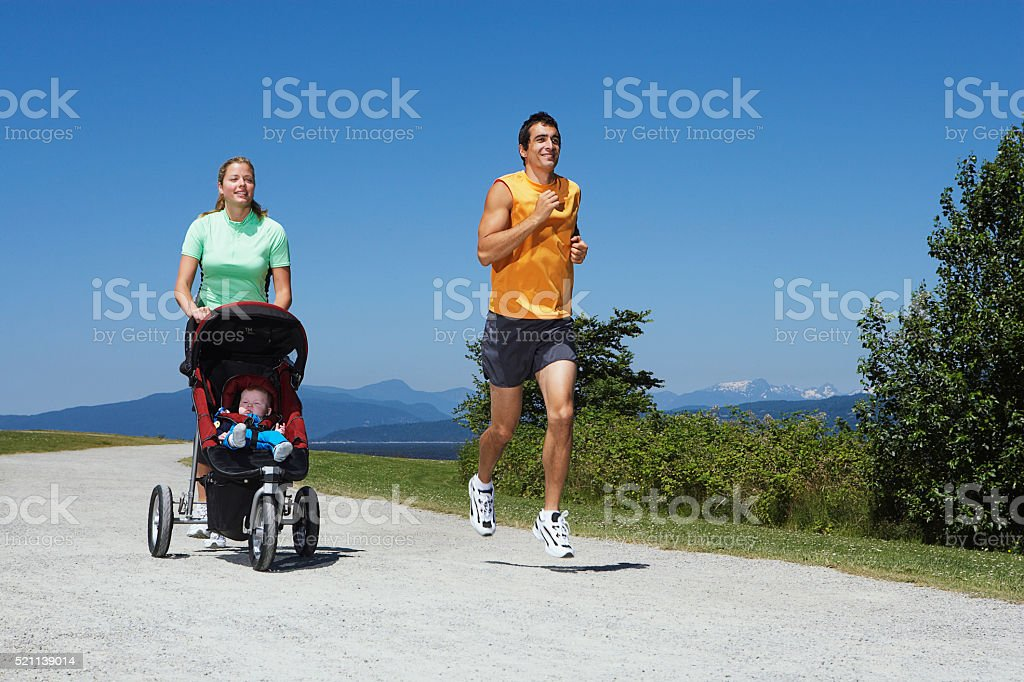 Couple jogging while pushing a baby stroller stock photo