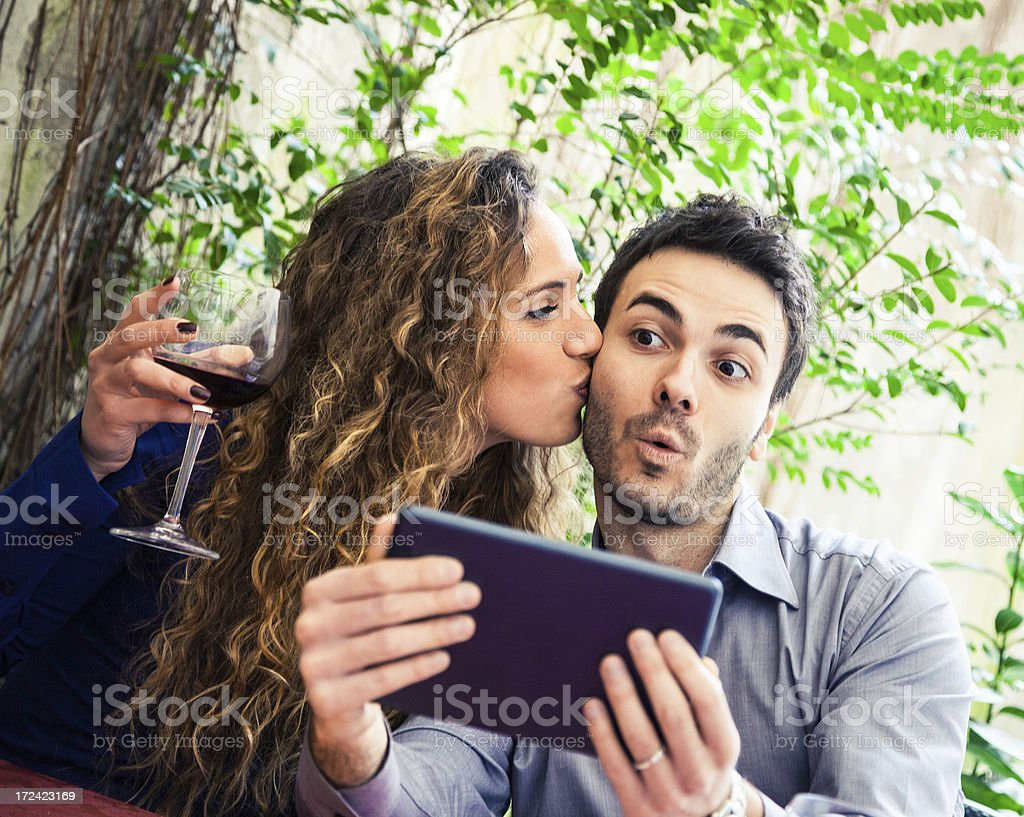 Couple joking on social networks at restaurant royalty-free stock photo