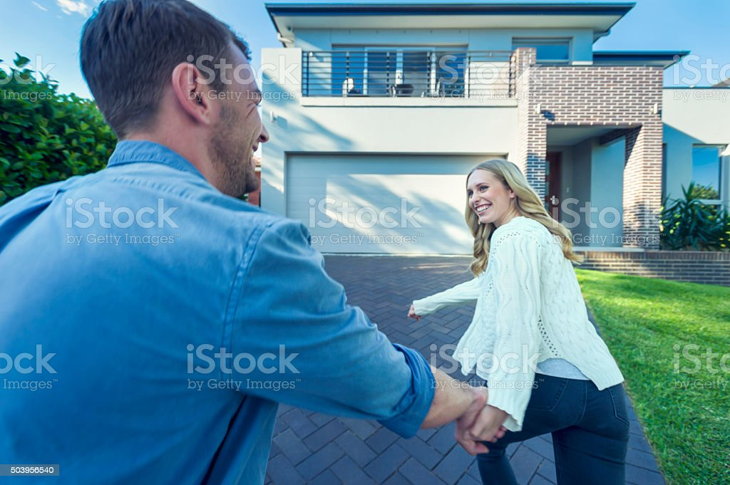 Couple joyfully running into their new home. stock photo