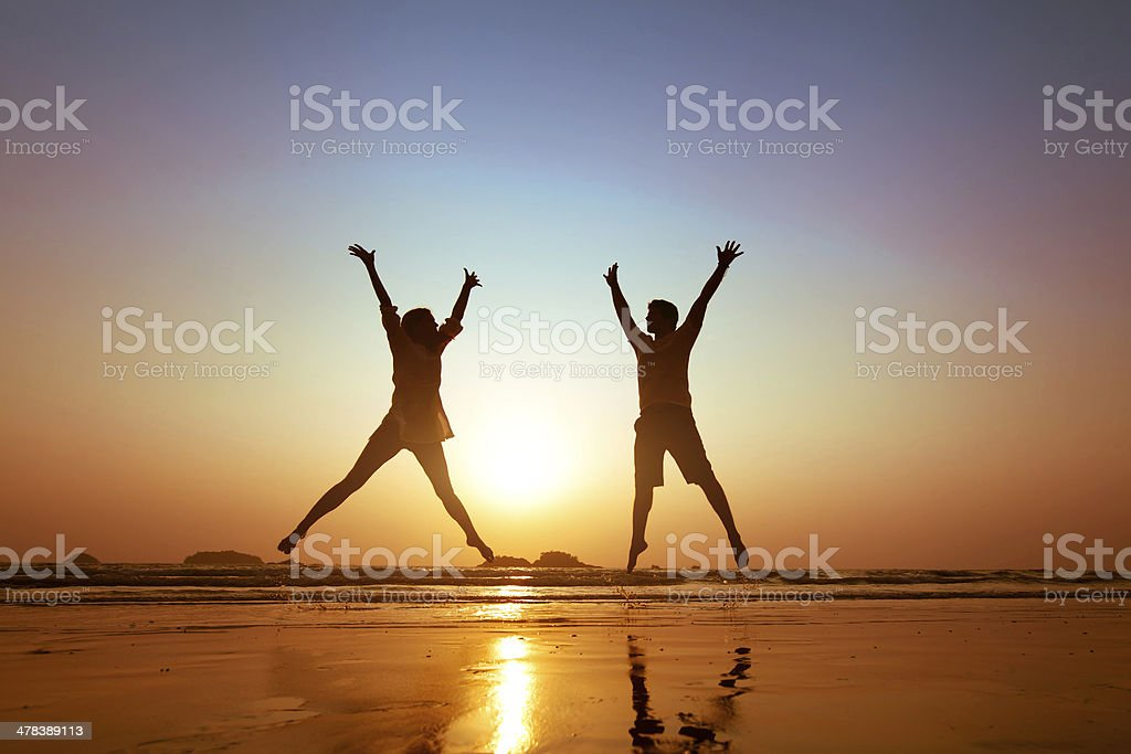 couple jumping at sunset stock photo
