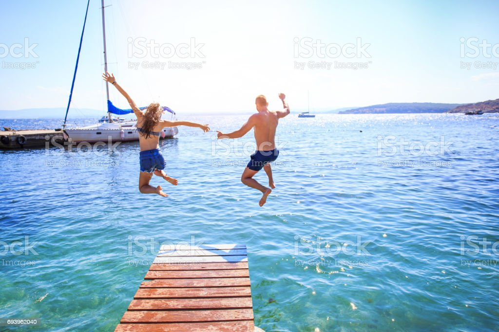 Couple jumping into water stock photo