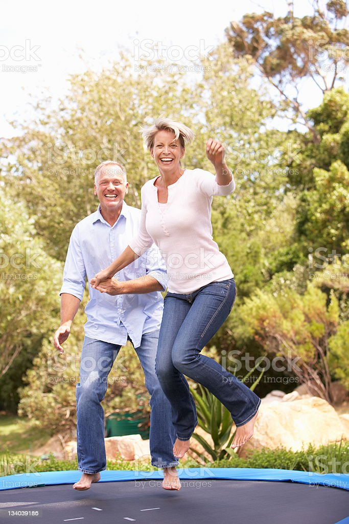 Couple Jumping On Trampoline In Garden stock photo