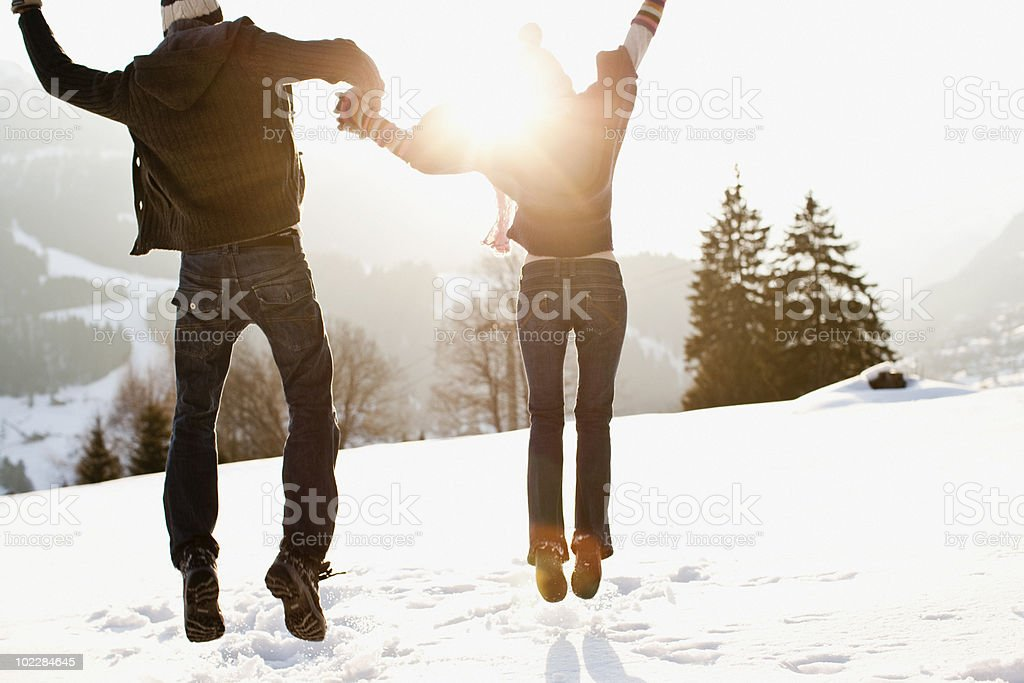 Couple jumping outdoors in snow stock photo