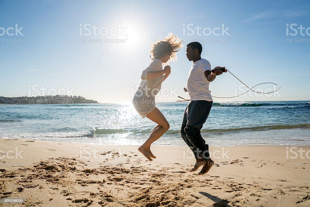 Couple jumping rope at the beach stock photo