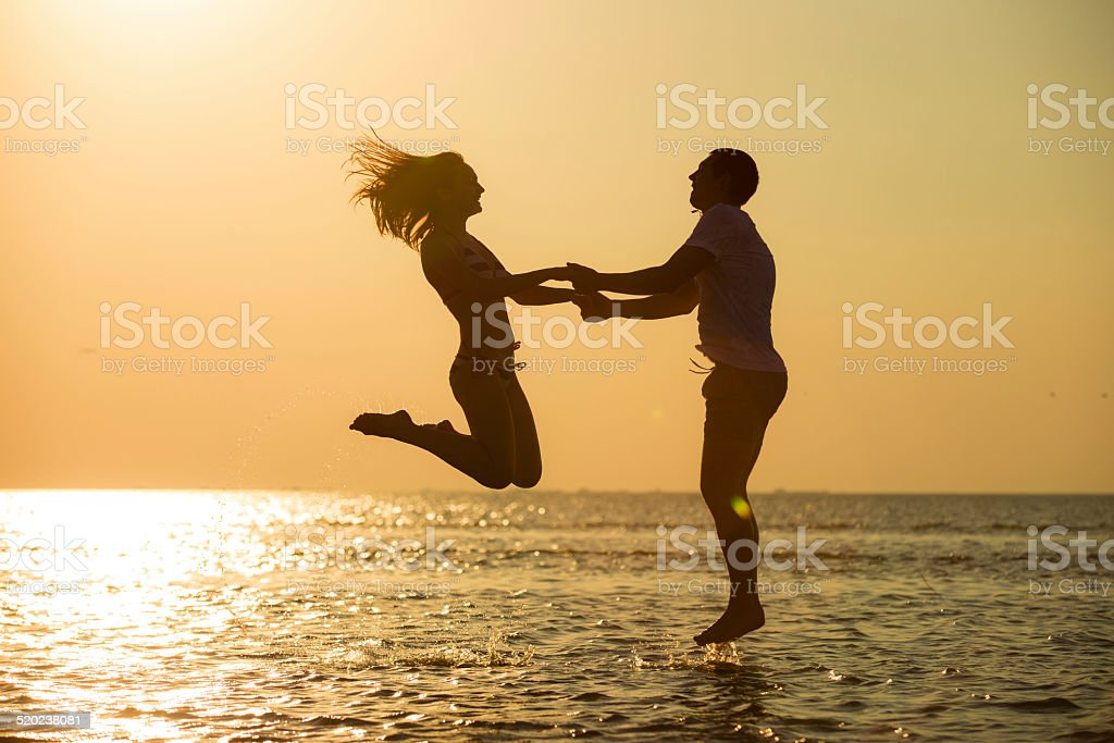 Couple jumping to the sky at sunset royalty-free stock photo